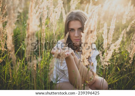 girl with long hair in a field with ears