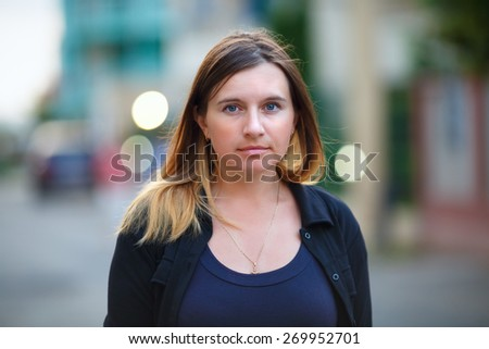 Girl with long hair on a background blur bokeh. Woman looking into the camera. Shallow depth of field. Focus on the model's face. - stock photo