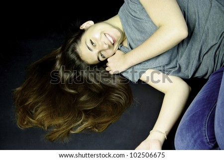Girl with long hair on the ground smiling