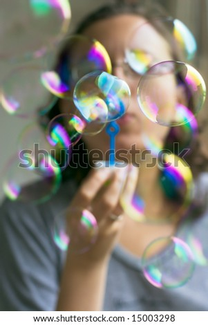 Girl with lot of colorful soap bubbles - stock photo