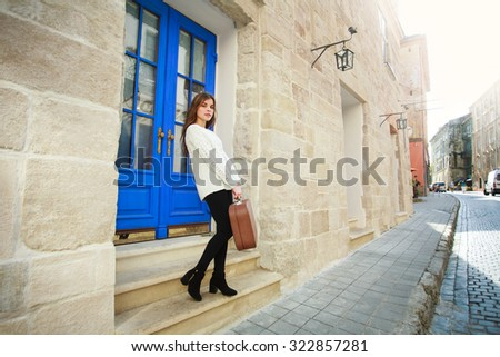 Girl with luggage left her house on the street of the old town, for the journey - stock photo