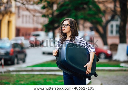 Girl with luggage walking through city street - stock photo
