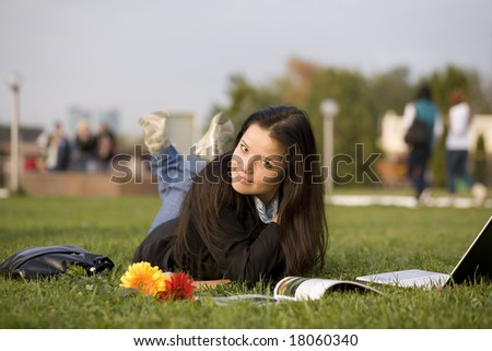 Girl with magazine and laptop on grass, campus - stock photo