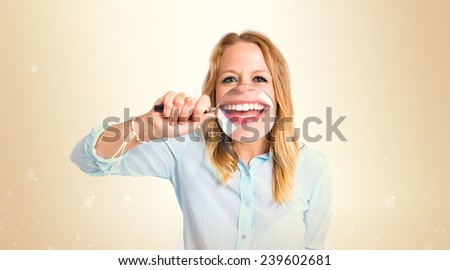 Girl with magnifying glass over ocher background - stock photo