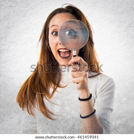 Girl with magnifying glass over textured background