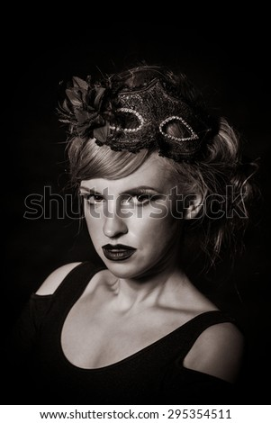 Girl with makeup and gothic masquerade mask close-up portrait. Low key. - stock photo