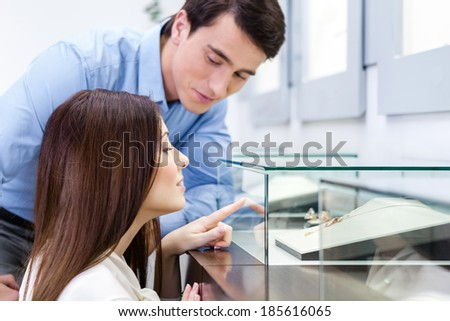 Girl with male selects expensive jewelry at jeweler's shop. Concept of wealth and luxurious life