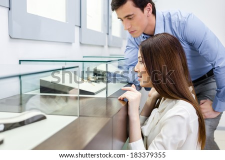 Girl with man chooses expensive jewelry at jeweler's shop. Concept of wealth and luxurious life
