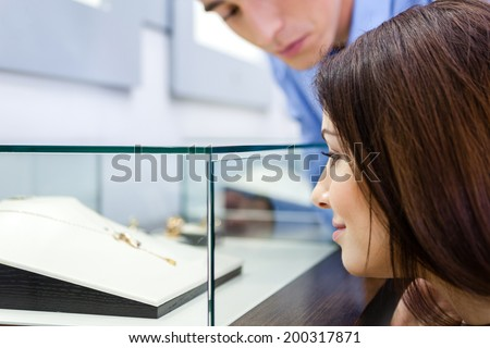 Girl with man selects expensive jewelry at jeweler's shop. Concept of wealth and luxurious life