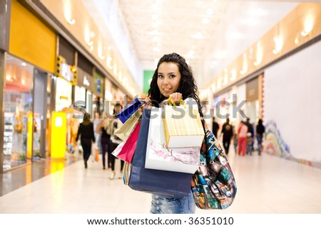 girl with many bags in hand stand in mall - stock photo
