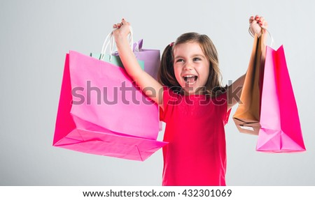 Girl with many shopping bags over grey background - stock photo