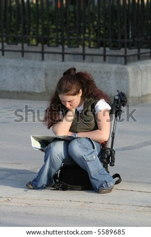 Girl with map tries to find right orientation - stock photo