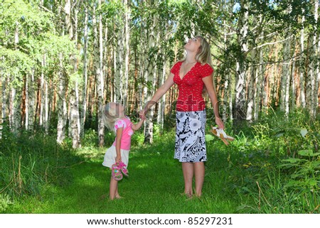girl with mother in green forest - stock photo