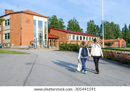 Girl with mother on the way to school  - stock photo