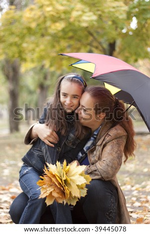 Girl with mother under umbrella. yellow leaves at autumn - stock photo