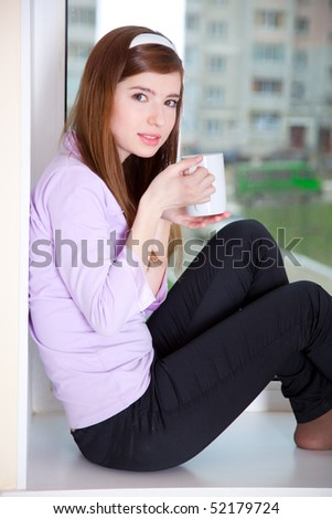Girl with mug of coffe is sitting on a window
