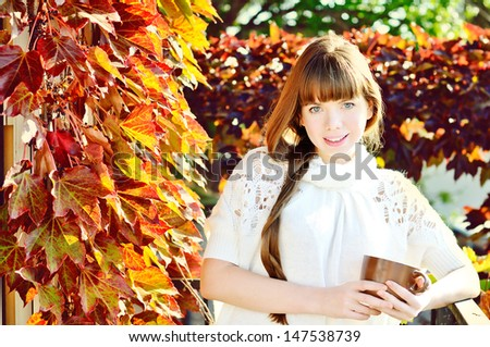 girl with mug of hot drink in sunny day - stock photo