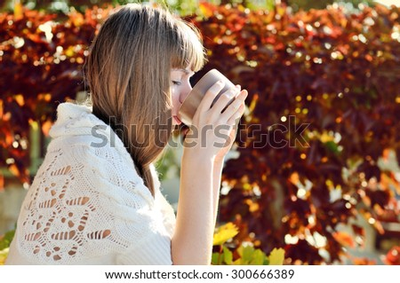 girl with mug of hot drink in sunny fall day - stock photo