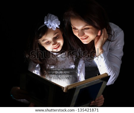 Girl with my mother found a wonderful book. - stock photo
