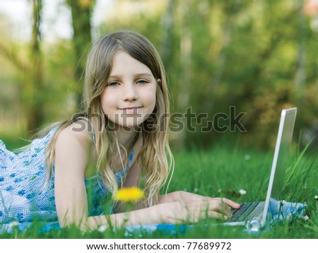 Girl with notebook computer on green meadow - stock photo