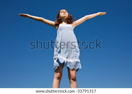 Girl with open arms against the blue sky