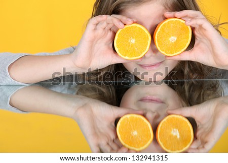 Girl with orange halves in front of her eyes - stock photo