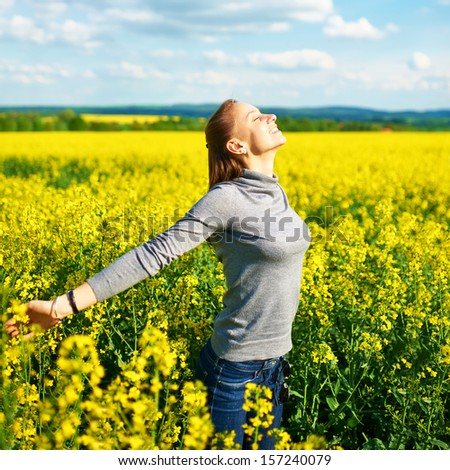 Girl with outstretched arms at colza field