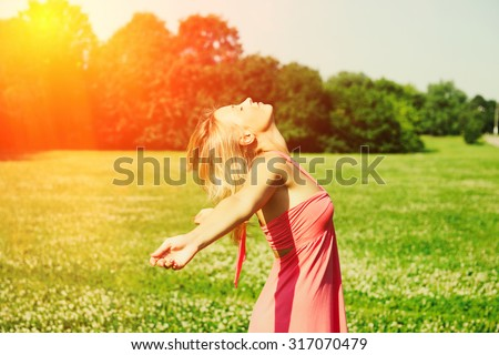 Girl with outstretched arms outdoors - stock photo