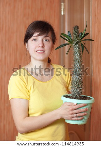 Girl with Pachypodium cactus in the pots at her home