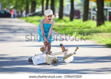 Girl with pain in leg after falling down from bicycle - stock photo