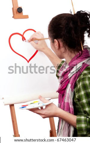 Girl with paint brush near easel, painting red heart on canvas.