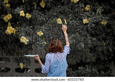 Girl with paintbrush painting yellow flower on background .
