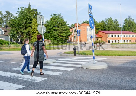 Girl with parent crossing street  - stock photo