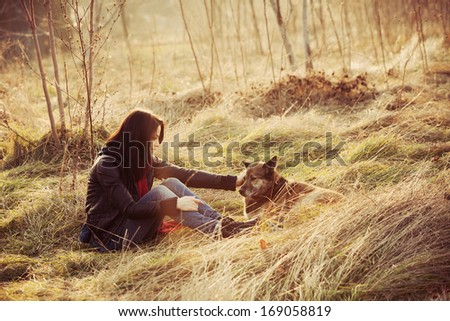 girl with pariah dog sit in yellow grass warm winter day retro colors - stock photo