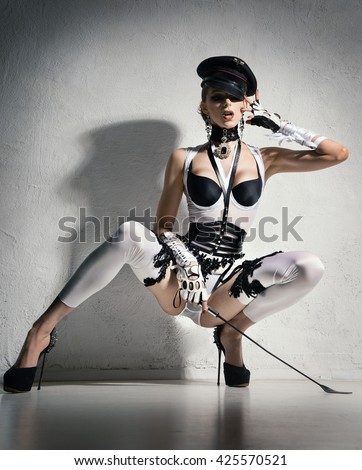 Girl with perfect waist in white lingerie and cap sitting with a whip