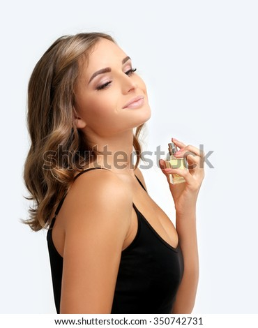 Girl with perfume,  woman holding bottle of perfume and smelling aroma - stock photo