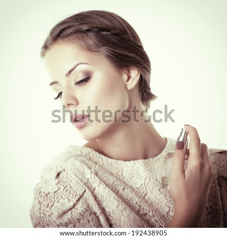 Girl with perfume, young beautiful woman holding bottle of perfume and smelling aroma, toned - stock photo