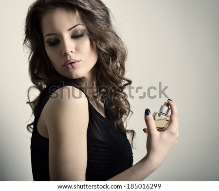 Girl with perfume, young beautiful woman holding bottle of perfume and smelling aroma, toned soft beige. - stock photo
