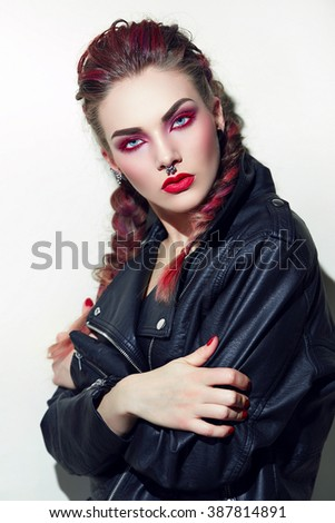 Girl with piercings on face. Makeup with rock style. Volume hair,plaited braids. Stands on white background in studio,looking into camera,arms folded across chest. Leather jacket. Painted in red hair.