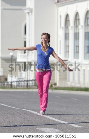 Girl with pigtails on open air. Young woman in pink trousers walking along the carriageway - stock photo