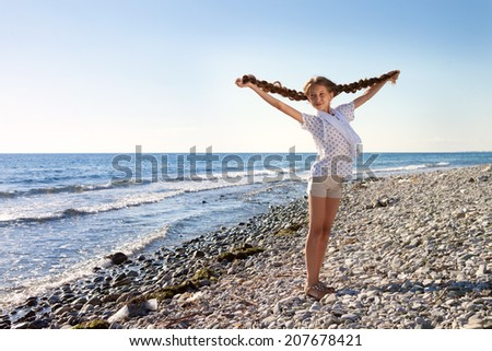Girl with pigtails resting on the beach