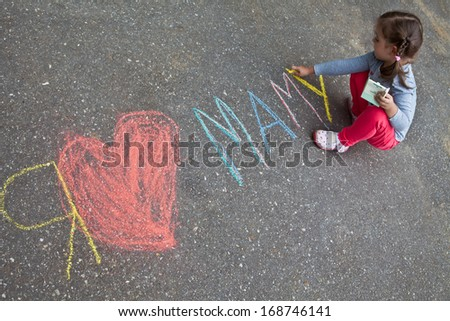 "Girl with pigtails wrote in chalk on the pavement, ""I love mom"" - stock photo"