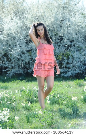 girl with pink dress walking in a field of daisies - stock photo