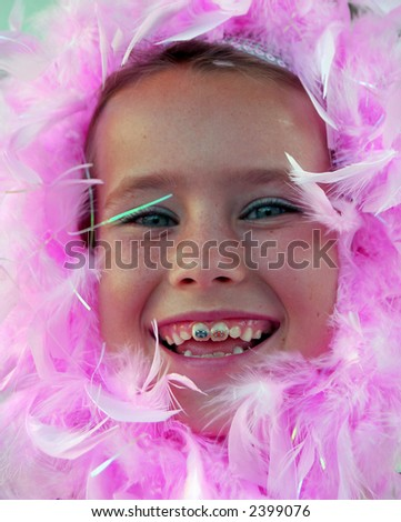Girl with pink feather boa wrapped around her face. - stock photo