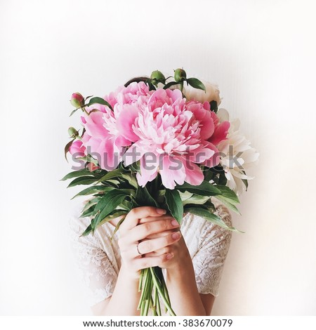 Girl with pink peonies bouquet at white wall - stock photo