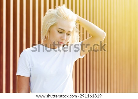 Girl with platinum blond hair in white t-shirt on woden background with flare - stock photo