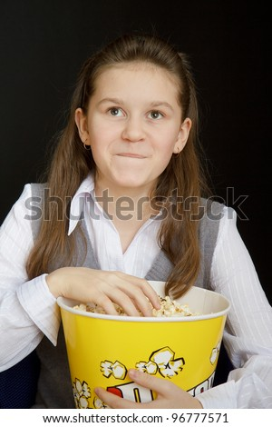 girl with popcorn on a black background - stock photo