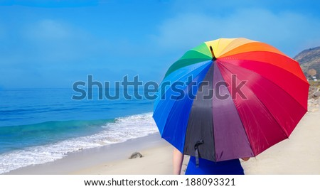 Girl with rainbow umbrella by the ocean - stock photo