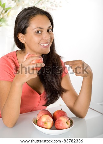 girl with red apple at home - stock photo