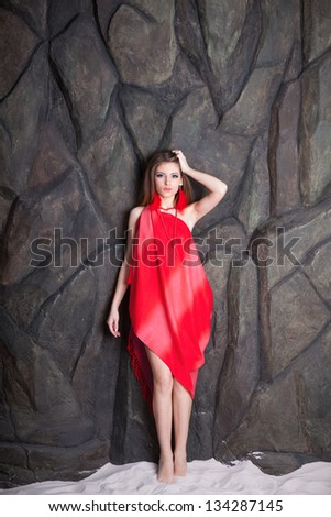 Girl with red feather earrings and pearl necklace posing over stone background - stock photo